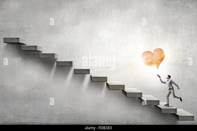 Gesamte Länge der Schüler läuft auf Leiter mit Buch in der hand Stockbild