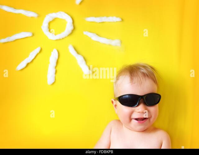 kleiner Junge mit Sonnenbrille und Sonne Form Stockbild