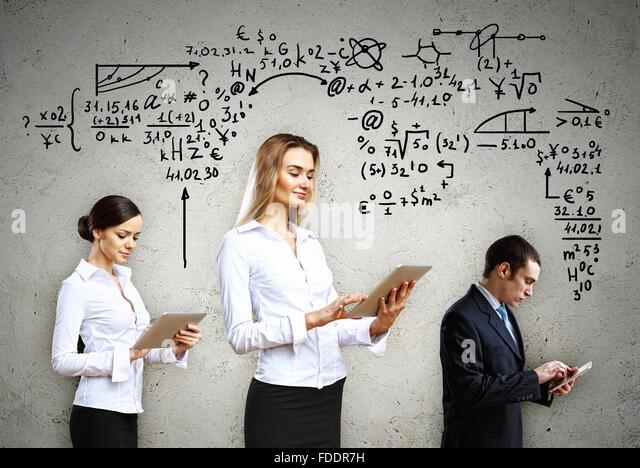 Drei junge Leute mit Tablet-pc in Händen gegen Zeichnungen im Hintergrund Stockbild