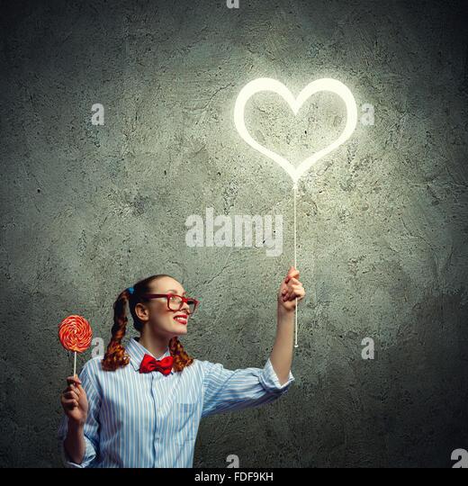 Teenager-Mädchen im roten Brille mit Süßigkeiten. Liebe-Konzept Stockbild