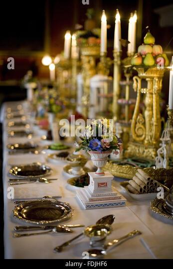 Esstisch und Kandelaber mit Blumenarrangements und Geschirr im Speisesaal an Attingham Park, Shrewsbury, Shropshire. Stockbild