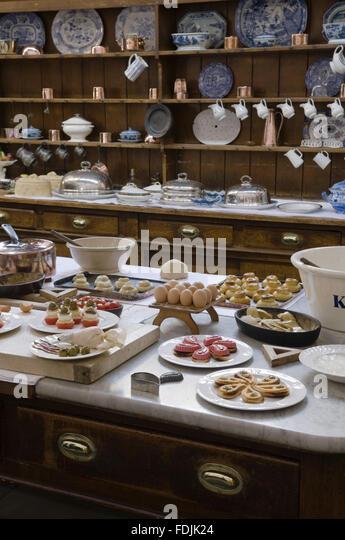 Tisch in der Küche mit Geschirr und Gebäck mit der Kommode hinter bei Lanhydrock, Cornwall beladen. Stockbild