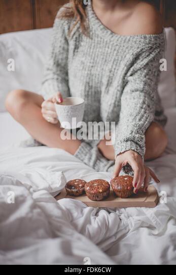 Frau sitzt auf dem Bett mit Tee und muffins Stockbild