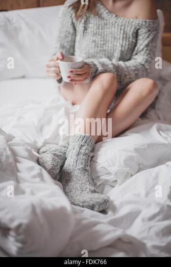 Frau im Bett mit einer Tasse Tee Stockbild