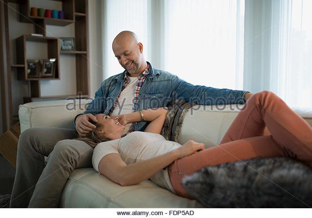 Frau, die Verlegung auf Ehemänner Runde Wohnzimmer sofa Stockbild