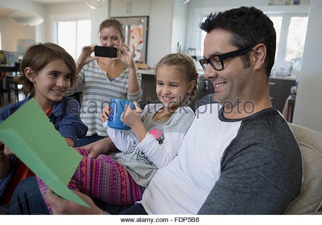 Vater öffnen Geburtstagskarte auf sofa Stockbild