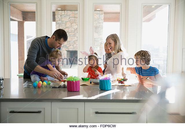 Familie in Küche Ostereier färben Stockbild