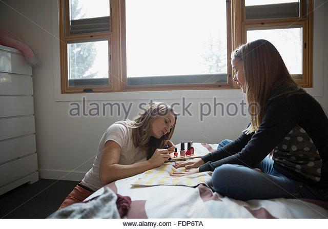 Mutter malen Töchter Fingernägel auf Bett Stockbild