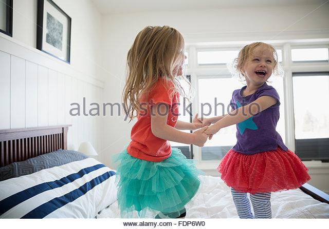 Verspielte Schwestern Hand in Hand und springen auf Bett Stockbild