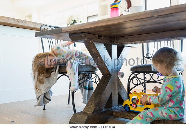 Mädchen im Schlafanzug spielen unter Esstisch Stockbild