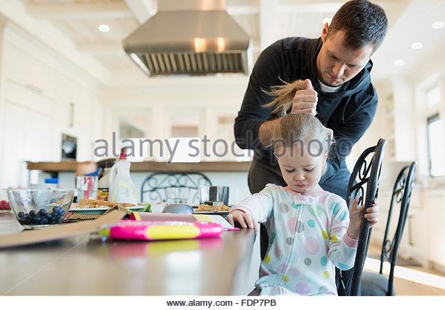 Vater, Töchter Haar am Tisch fixieren Stockbild