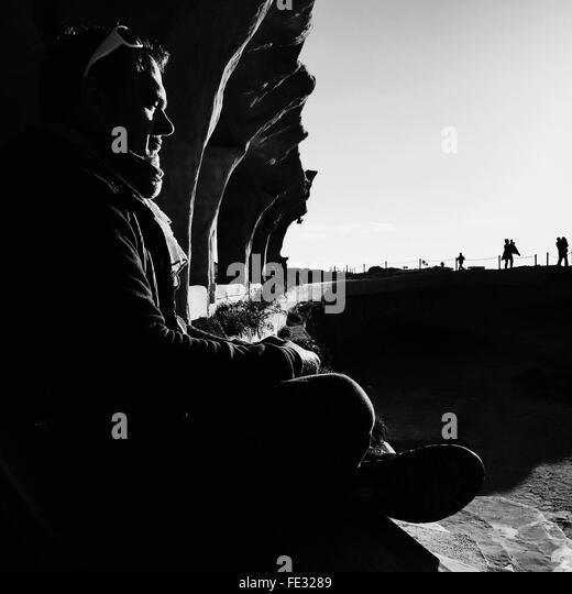 Seitenansicht der Mann Meditation am Strand von Cala Comte an sonnigen Tag Stockbild