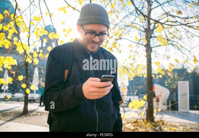 Lächelnd Mitte erwachsenen Mann mit Handy auf Fußweg Stockbild