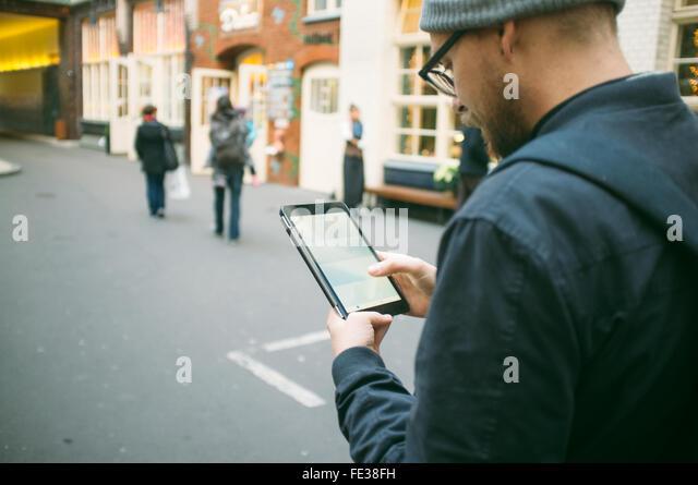 Mitte erwachsener Mann mit Digital-Tablette auf Straße Stockbild