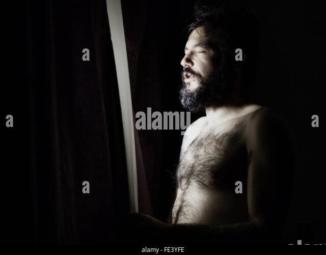 Mann steht am Fenster mit Augen geschlossen Stockbild