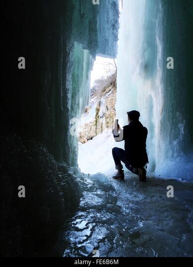 Rückansicht des Menschen fotografieren gefrorenen Wasserfall Stockbild