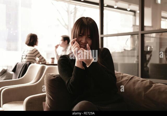 Porträt der Frau sitzt auf dem Sofa im Cafe Stockbild