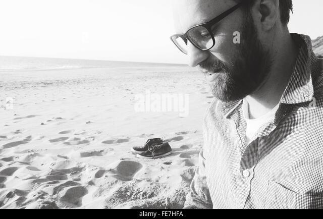 Seitenansicht des jungen Mannes auf der Suche nach unten stehend am Strand Stockbild