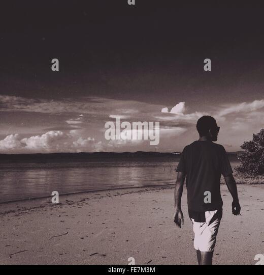 Rückansicht des Mannes zu Fuß am Strand gegen Himmel Stockbild