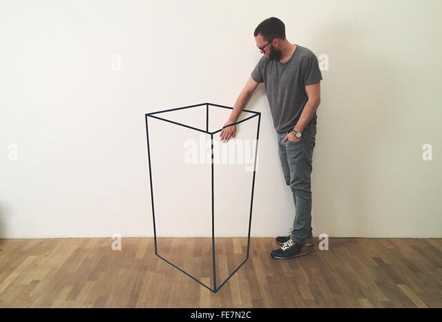 Optische Täuschung der Mitte erwachsener Mann Hand im Container gegen weiße Wand einfügen Stockbild