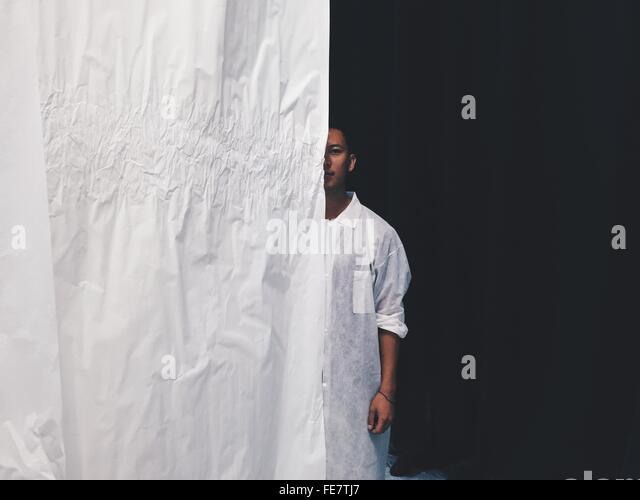 Porträt des jungen Mann hinter dem Vorhang Stockbild