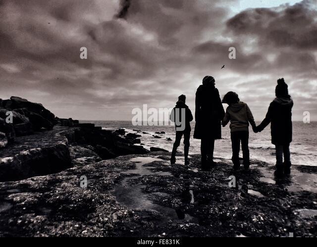Silhouette der Familie am Strand Küste stehen Stockbild