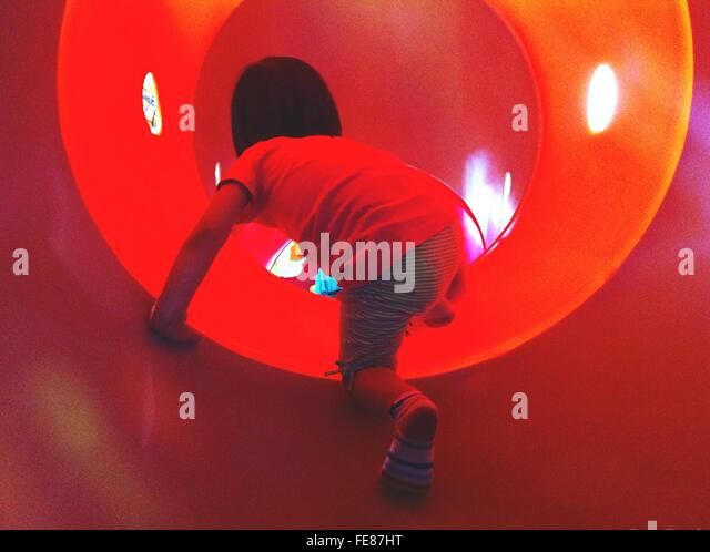 Junge im Tunnel am Spielplatz Stockbild