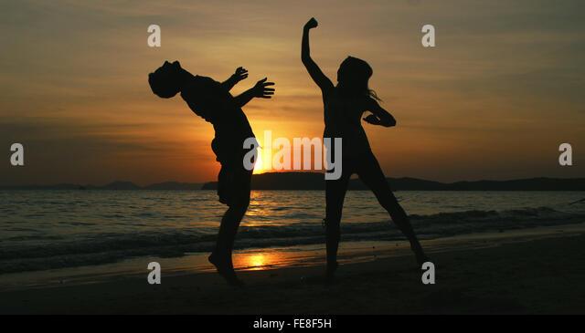 Silhouette Frau trifft Mann am Strand bei Sonnenuntergang Stockbild