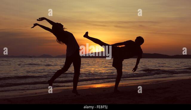 Silhouette-Mann schlägt Frau am Strand bei Sonnenuntergang Stockbild