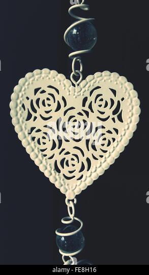 Herz-Form-Dekoration hängen auf schwarzem Hintergrund Stockbild