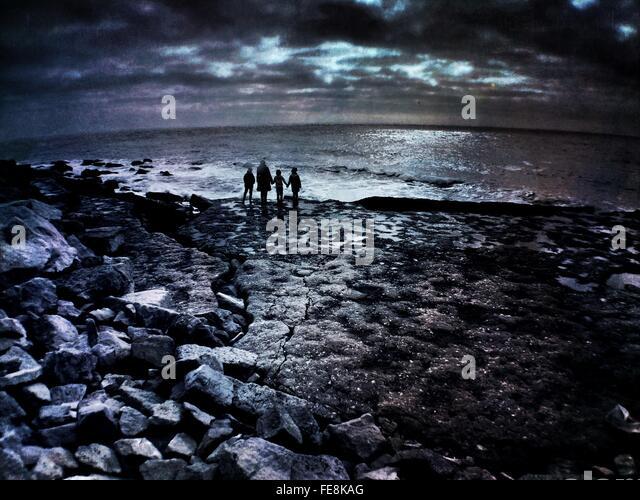 Silhouette-Familie am Ufer von Felsen gegen bewölktem Himmel Stockbild