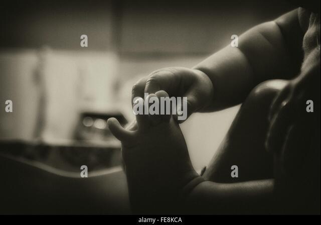 Baby Holding Füße zu Hause Stockbild