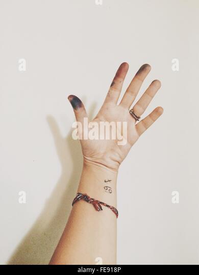 Hand der Frau mit Tattoo und schmutzigen Fingern Stockbild