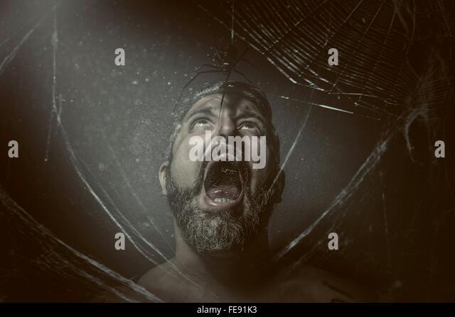 Mann mit offenem Mund Blick auf Spinne vor schwarzem Hintergrund Stockbild