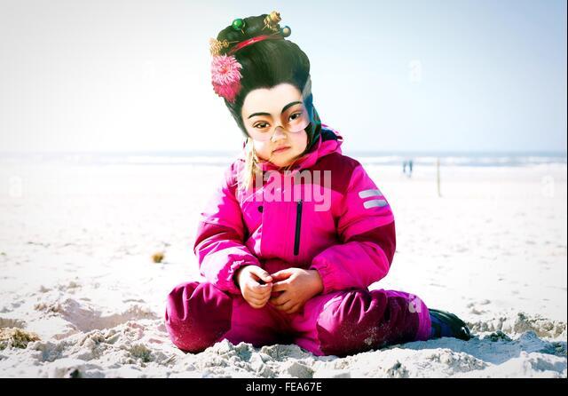 Kind mit Maske am Sandstrand Stockbild