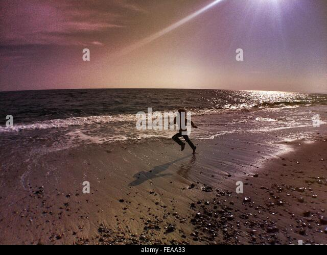 Sonnigen Tag am Strand gegen Himmel laufen junge Stockbild