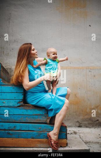 Cute 1 Jahr Baby stehend auf Mutters Knie. Familie Kleidungsstil mit blauen Farben. Selektiven Fokus auf Mutter. Stockbild