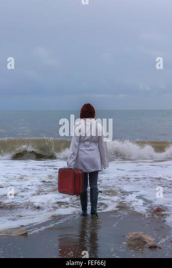 eine Frau in einem weißen Mantel mit einem roten Koffer am Meer im winter Stockbild
