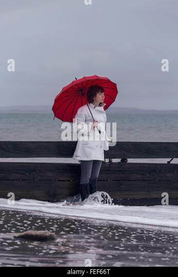 eine Frau in einem weißen Mantel mit einem roten Regenschirm am Meer im winter Stockbild
