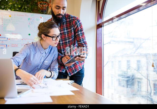 Zwei junge Frau und Mann Modedesigner arbeiten und mit tablet zusammen Stockbild