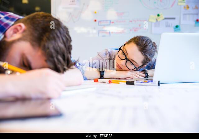 Erschöpft, junge Frau und Mann schlafen auf dem Tisch im Büro Stockbild