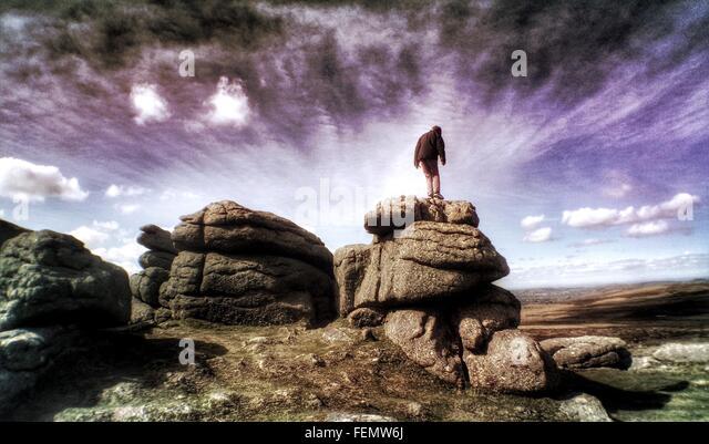 Niedrigen Winkel Blick auf Felsen stehende Person Stockbild