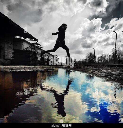 Man springt über Stream Stockbild