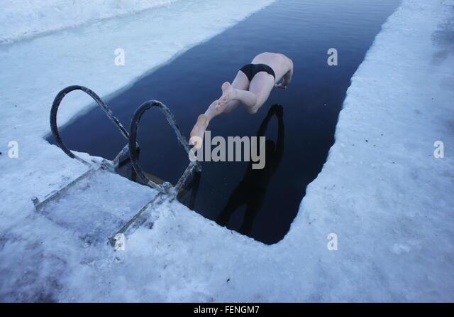Voller Länge des Menschen Tauchen In gefrorenen Schwimmbad Stockbild
