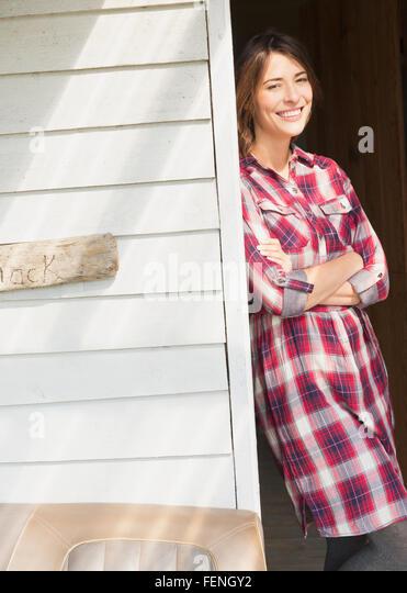 Porträt lächelnde Brünette Frau im karierten Kleid in sonnigen Tür Stockbild