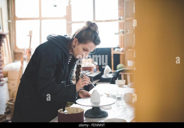 Seitenansicht der jungen Frau in Werkstatt Tontopf, Keramikglasur zuweisen blickte Stockbild