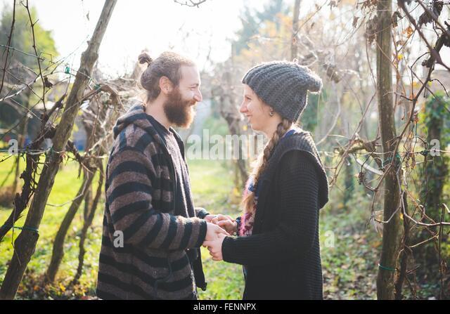 Seitenansicht des Paares unter Bäumen Angesicht zu Angesicht, Hand in Hand, Lächeln Stockbild