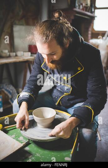 Mitte erwachsener Mann sitzt an der Töpferscheibe blickte auf Ton-Topf Stockbild