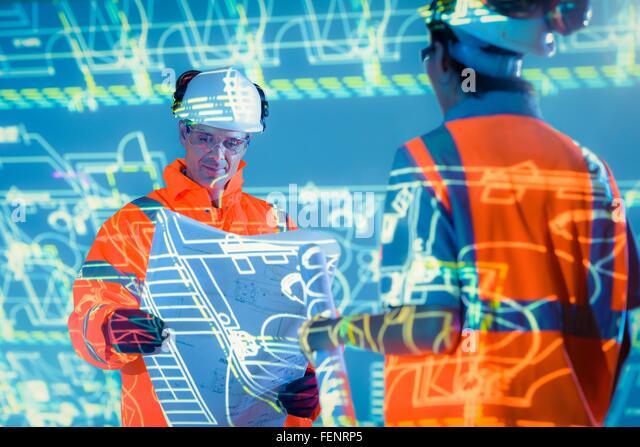 Ingenieure mit Blaupausen und projizierte Pläne Stockbild