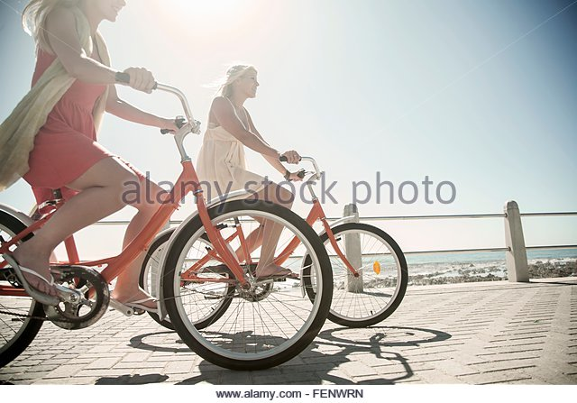Junge Frauen Radfahren am Meer, Cape Town, Südafrika Stockbild